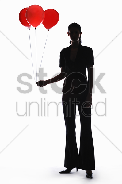 silhouette of businesswoman holding balloons stock photo