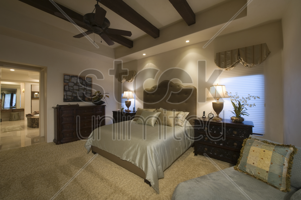 silk bed cover on double bed in palm spring bedroom with beamed ceiling stock photo