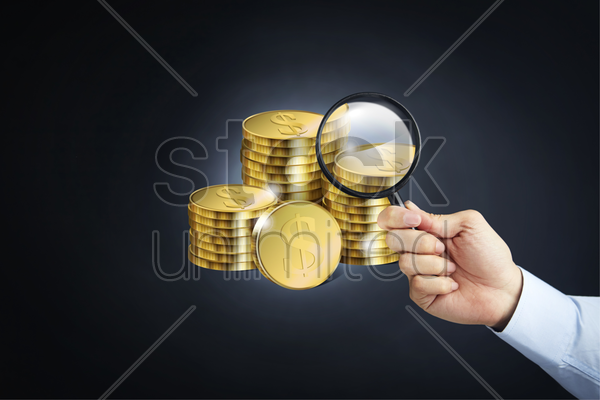stack of coins with a hand holding magnifying glass stock photo
