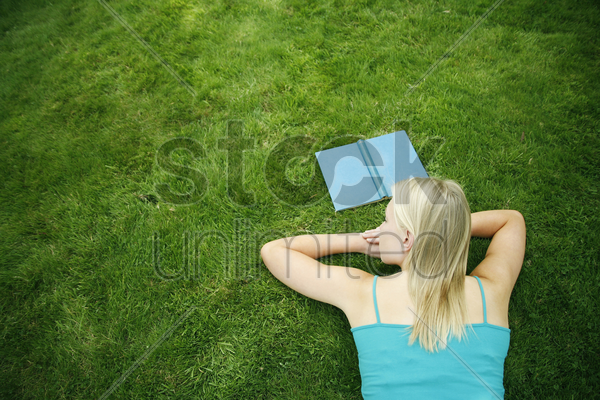 teenage girl lying forward on the field with book in front of her stock photo