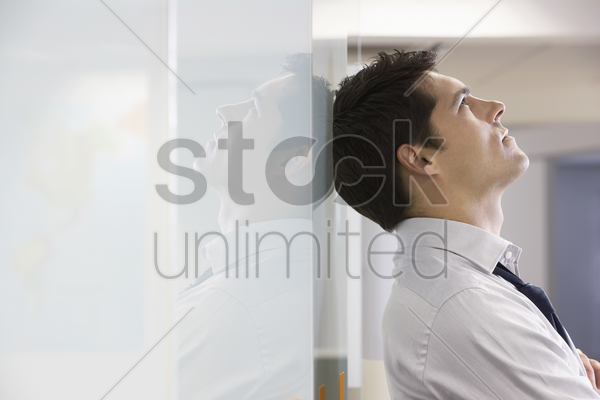 unhappy businessman leaning back against office wall and looking at ceiling side view stock photo