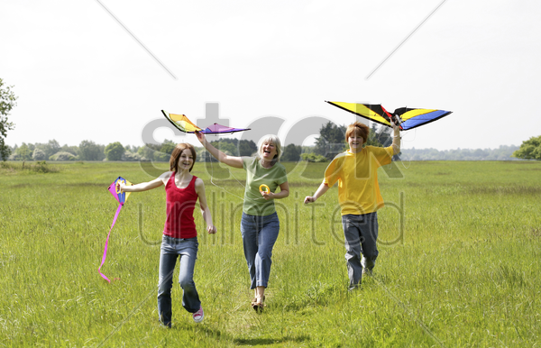 woman and her children flying kites stock photo
