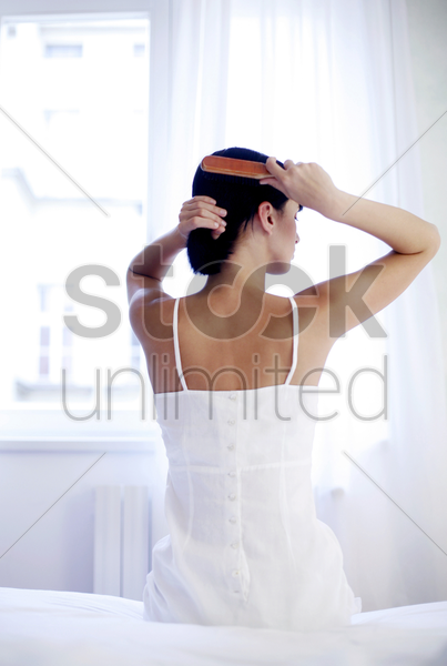 woman combing her hair stock photo