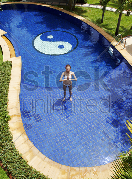woman practising yoga in the swimming pool stock photo