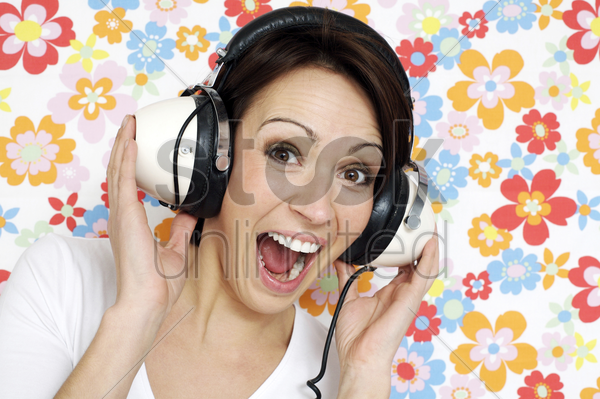woman smiling while listening to music on the headphones stock photo