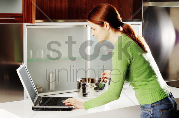 woman using laptop while cooking in the kitchen stock photo