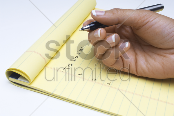 woman writing list of tasks to do close-up of hand stock photo