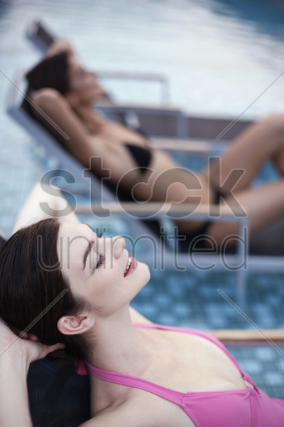 women relaxing on lounge chairs stock photo