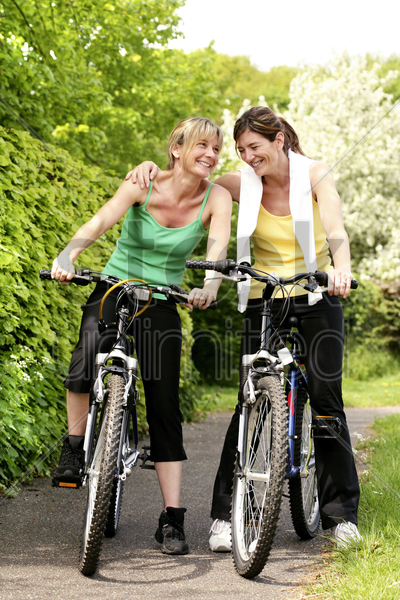 women sitting on bicycles stock photo