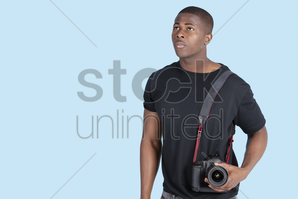 young african american man with digital camera looking up over blue background stock photo
