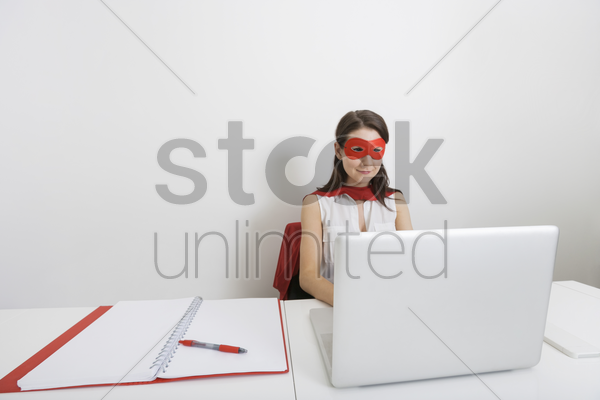 young businesswoman dressed as superhero using laptop at desk in office stock photo