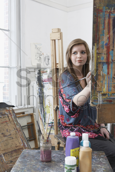 young female art student painting at easel in art studio stock photo