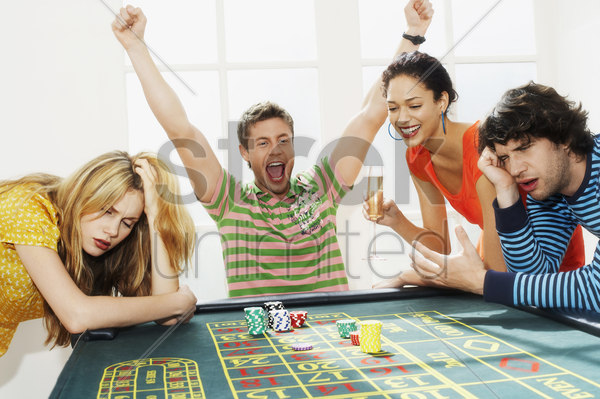 young man winning on roulette table while friends lose stock photo
