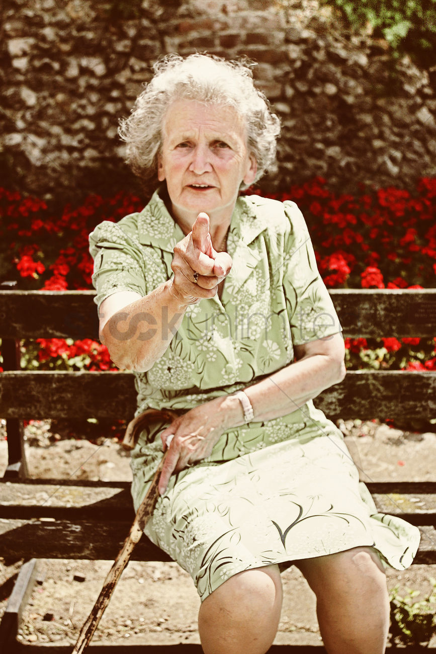 a grumpy old lady sitting on a bench holding her walking stick