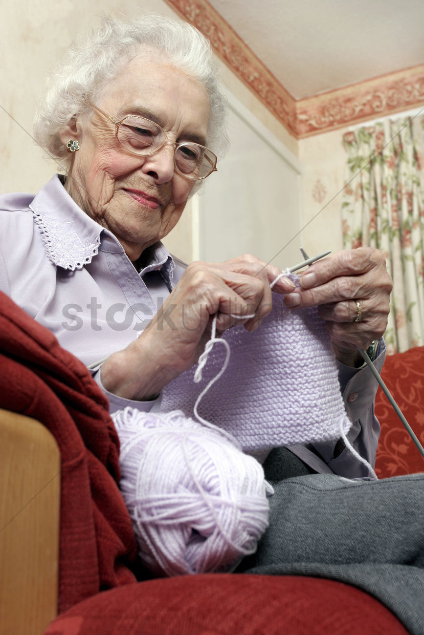 An Old Bespectacled Woman Sitting On The Couch Knitting Stock