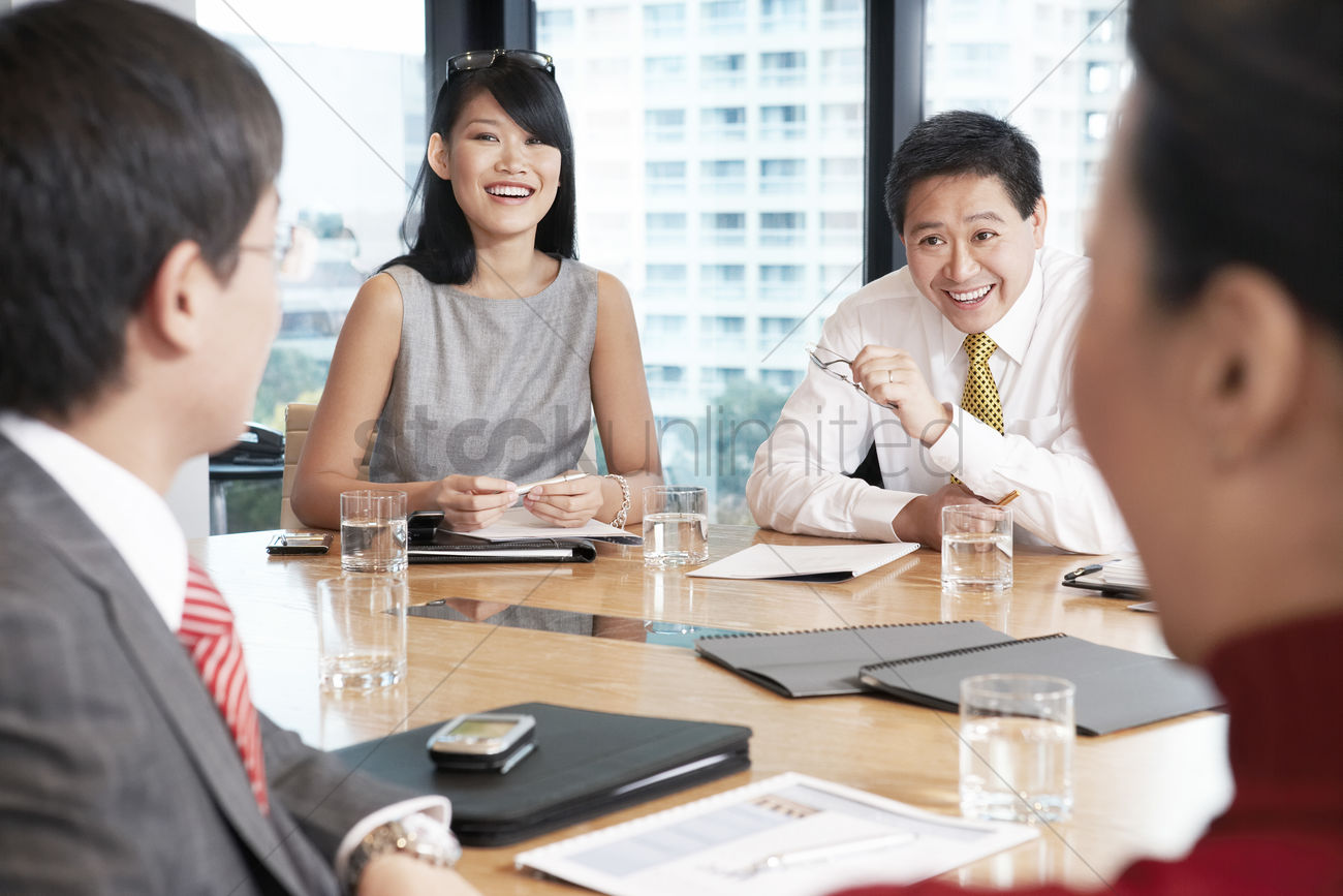 Business People Sitting Round Table In Conference Room Stock Photo
