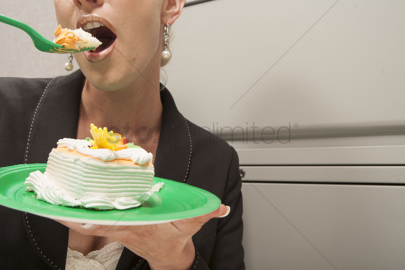 Sensational Business Person Eating Birthday Cake In Cubicle Stock Photo Funny Birthday Cards Online Inifofree Goldxyz