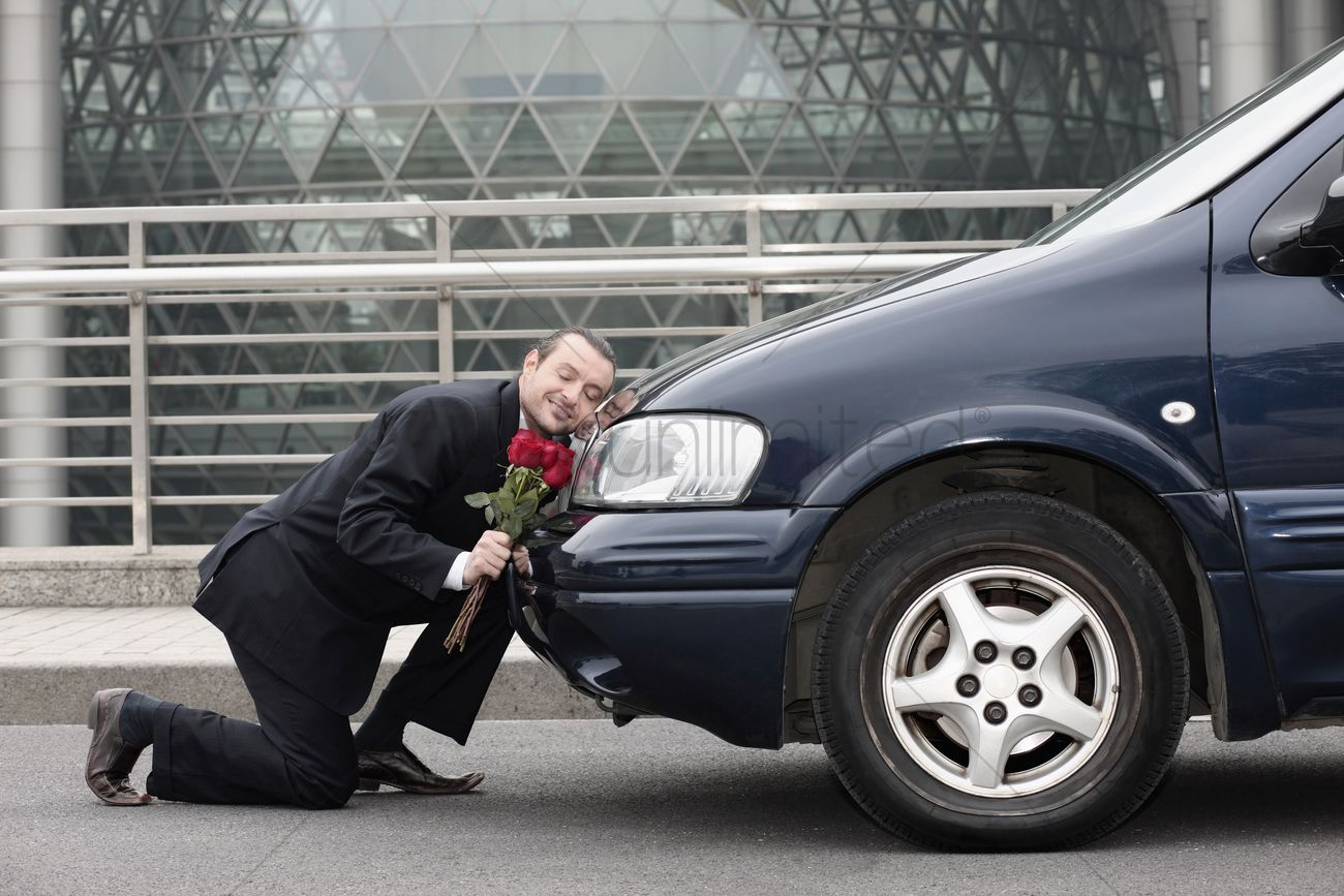 businessman-kneeling-and-resting-his-head-on-a-car-while-holding-flowers_1869063.jpg