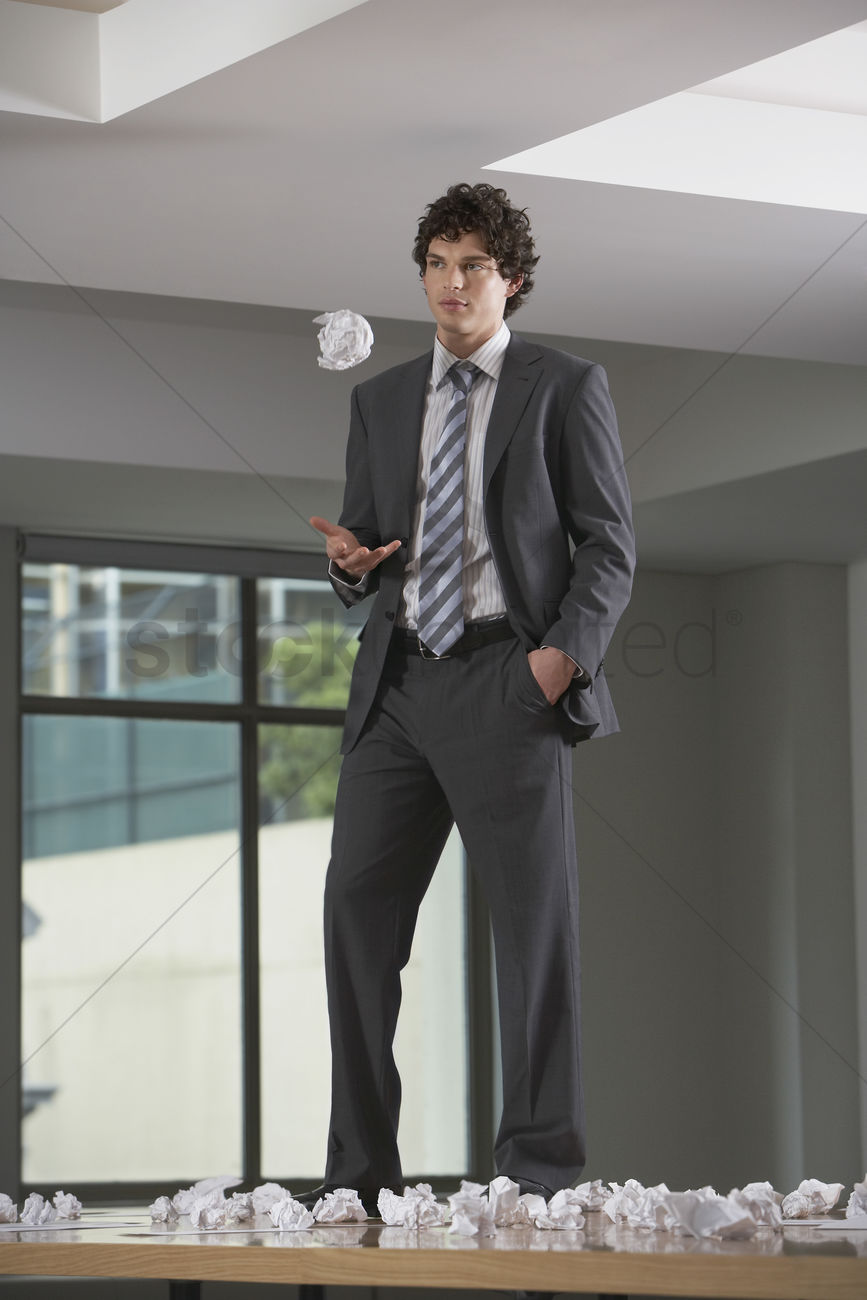 Businessman Standing On Conference Room Table With Crumpled Paper - Standing conference room table