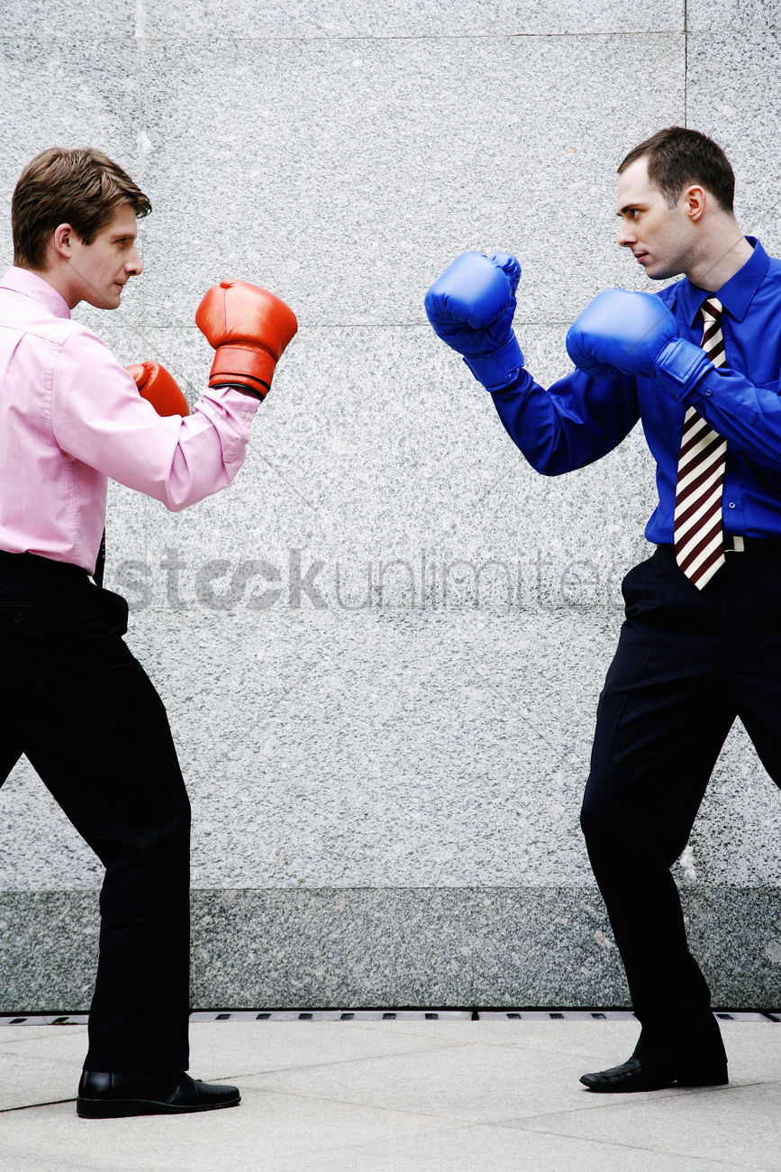 Businessmen with boxing gloves getting ready to fight ...