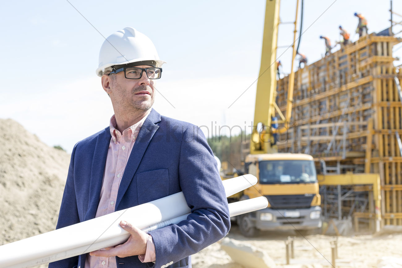 Confident architect holding rolled up blueprints at construction confident architect holding rolled up blueprints at construction site stock photo malvernweather