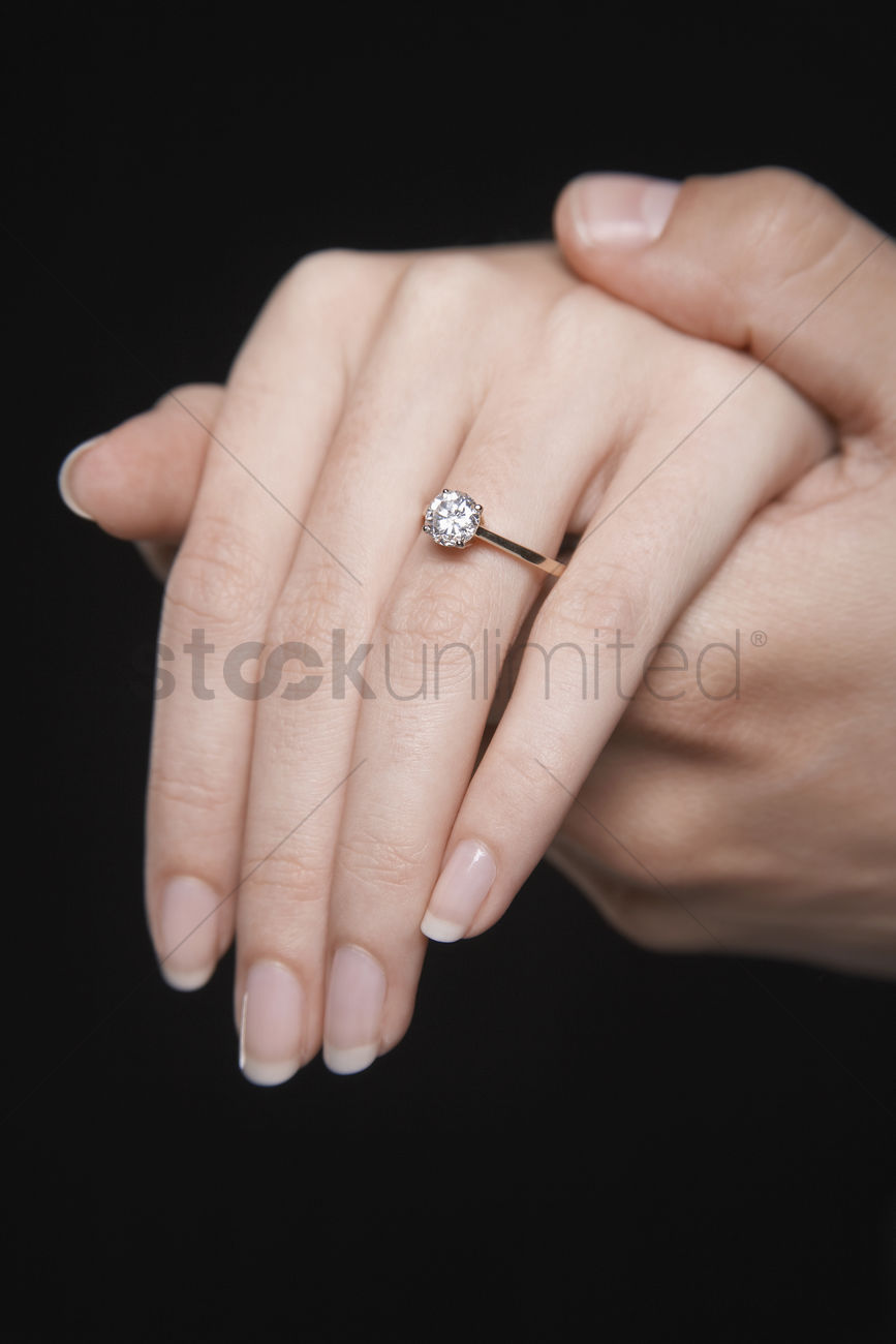Man holding woman\'s hand displaying engagement ring close up of hand ...