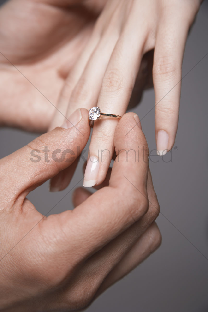 Man placing engagement ring on woman\'s finger close-up of hands ...