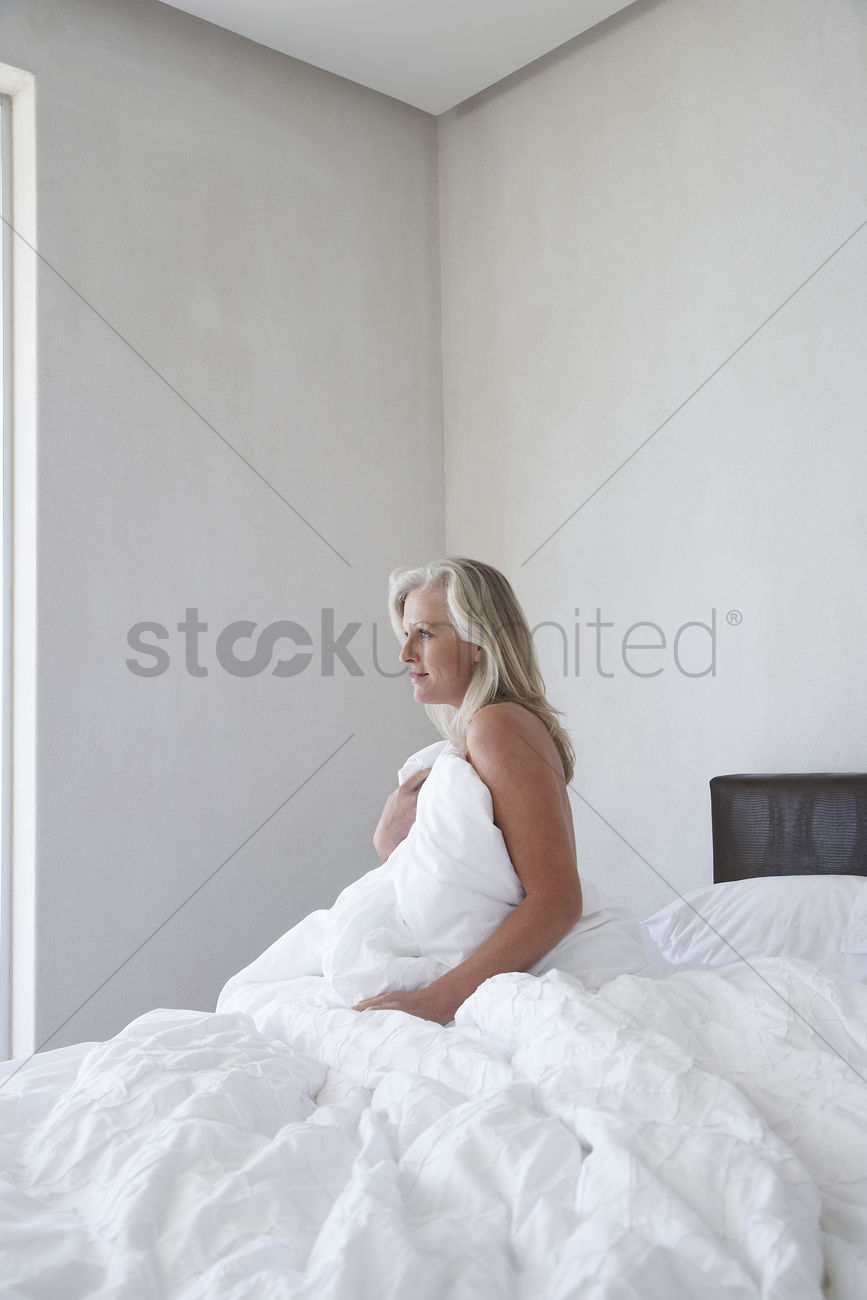 unmade bed side view. Mature Woman In Bathrobe Sitting Up Bed Holding Covers Over Chest Side View Stock Photo Unmade