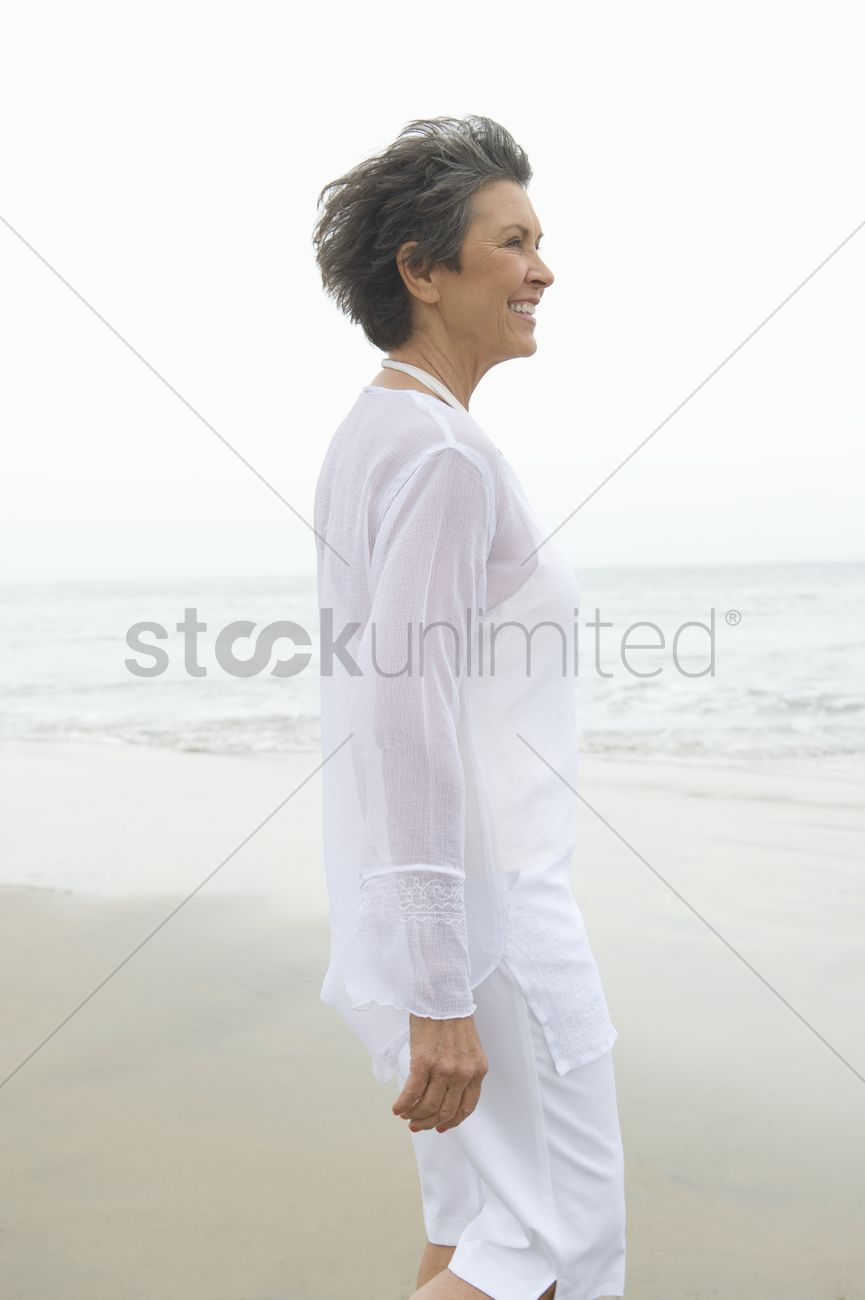 mature woman in white clothing at waters edge stock photo