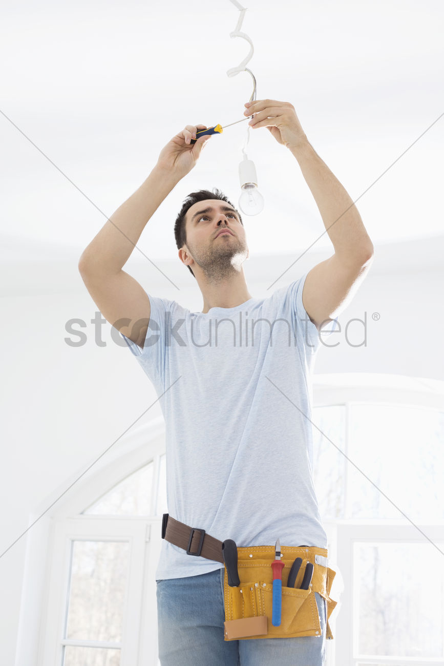 Mid Adult Man Fixing Light Bulb Wiring In New House Stock Photo A