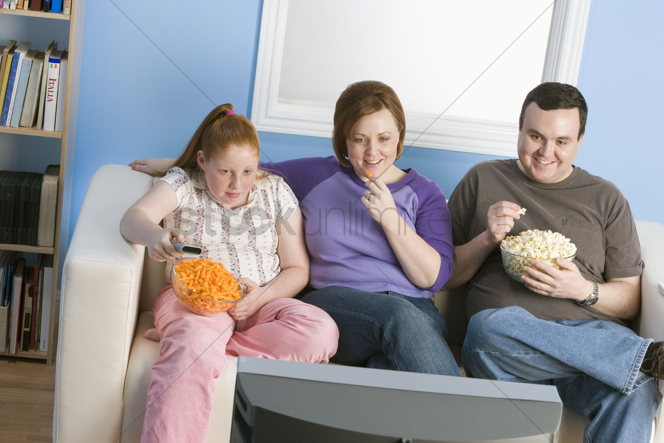 Overweight Family Watching Television On Sofa Stock Photo