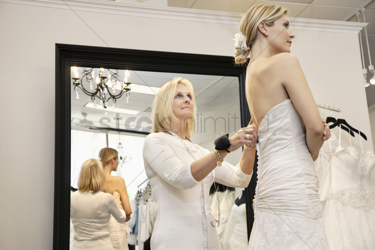 Senior Owner Isting Young Bride Getting Dressed In Wedding Gown Stock Photo