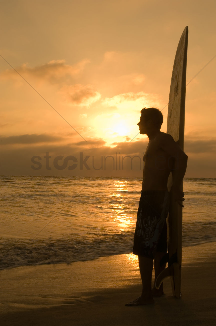 736092e8f8 surfer standing on beach leaning on surfboard watching sunset side view  stock photo