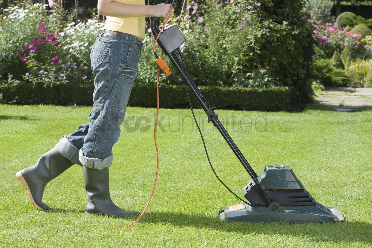 Hispanic Woman In Dress Pushing Lawn Mower High-Res Stock