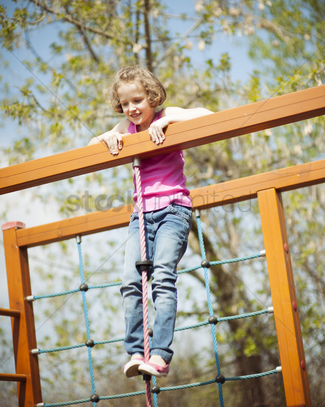 Young girl standing at top of rope and climbing frame Stock Photo ...