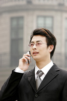 A bespectacled businessman talking on the hand phone