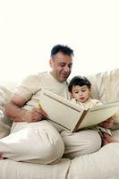 A man sitting on the couch reading a story book for his young son