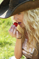 A woman in cowboy hat eating a strawberry