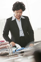 A woman in formal wear ironing clothes