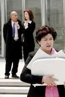 An angry woman carrying a briefcase of documents