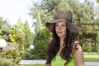 Attractive young woman wearing sunhat in park