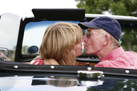 Back shot of a married couple kissing in the car