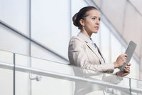 Beautiful young businesswoman holding digital tablet at office railing
