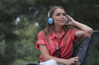 Beautiful young woman listening musing through headphones in park