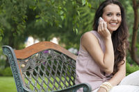 Beautiful young woman using cell phone on bench in park