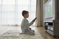 Boy  7-9  sitting on floor watching cartoons in television