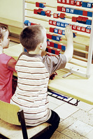 Boy and girl playing with big abacus