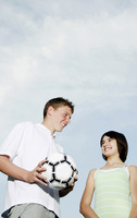 Boy holding soccer ball while smiling at his sister