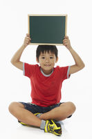 Boy sitting and holding up a blackboard