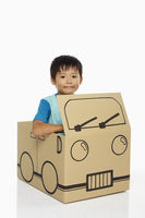 Boy sitting inside a cardboard bus
